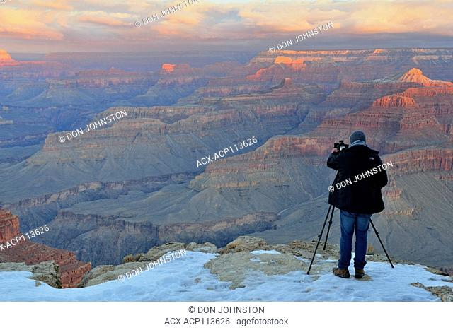 Photographer at the Grand Canyon at sunrise in winter, from Hopi Point, Grand Canyon National Park, Arizona, USA