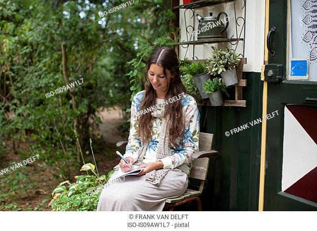 Young woman writing notes in cabin porch