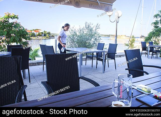 Illustrative photo, a waitress uses a hand disinfection, sprayer disinfectant solution for cleaning a table in a restaurant in Sali, sailing yacht, cruising