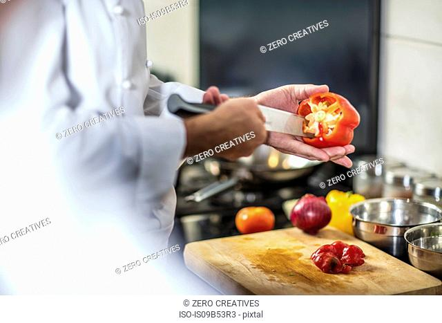 Chef de-seeding red pepper with knife
