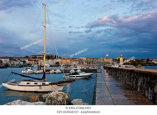 Early morning moody sunrise view of Desenzano del Garda in Italy, from the end of the quay with the lighthouse, sail boats and the town in the distance