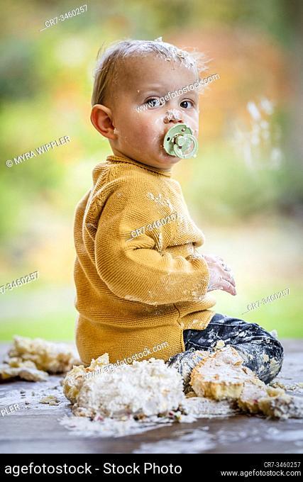 Baby boy having fun on his one year birthday, smashing a birthday cake