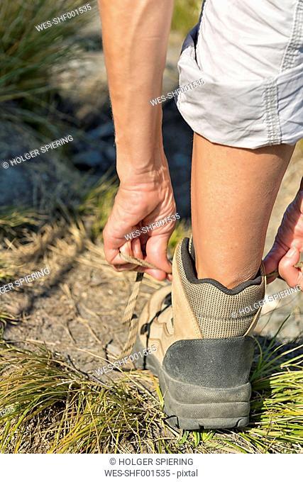 New Zealand, South Island, Tasman, Mount Arthur, woman tying her hiking boot
