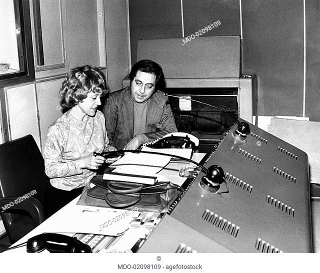 Italian TV host Corrado (Corrado Mantoni) and Italian director Gigliola Rosmini working at the Swiss TV show Cordialmente dall'Italia. Rome, 1970s