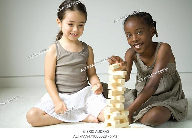 Two girls sitting on floor playing with blocks, one smiling at camera