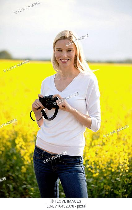 A young woman standing next to a rape seed field in flower, holding a camera