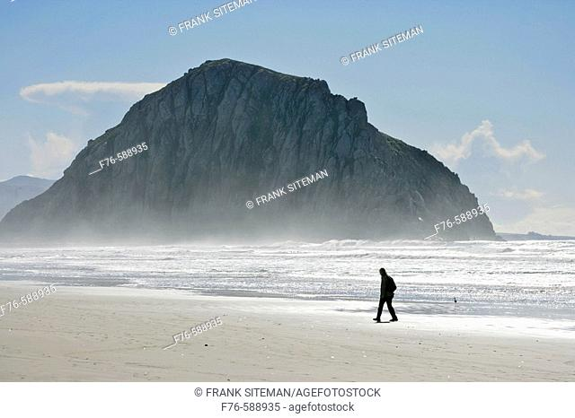 Woman walking through the salt air, sea spray on beach in front of Morro Rock, Morro Bay, CA