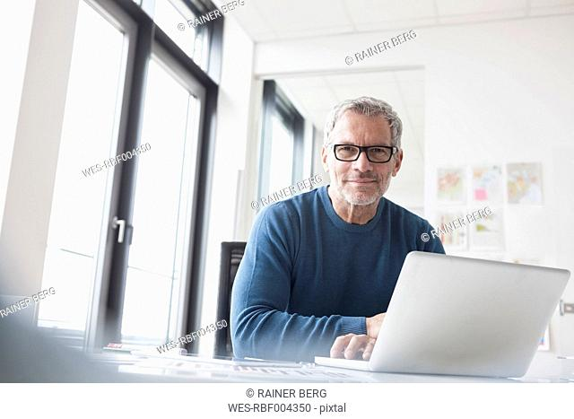 Mature man sitting in office using laptop