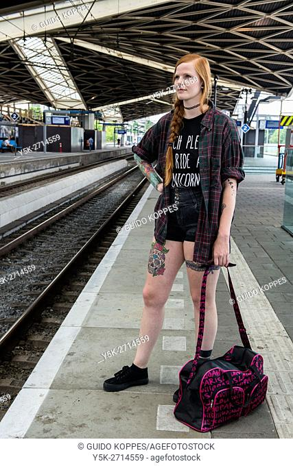 Tilburg, Netherlands. Young, red haired woman waiting on a railway station platform for her delayed, connecting commuter train home