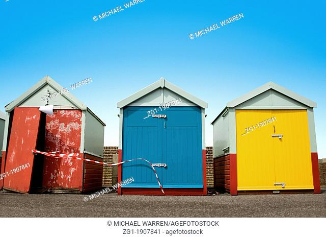 Three Beach huts in a Row With One Very Run Down Hut on Brighton Seafront, Sussex, England