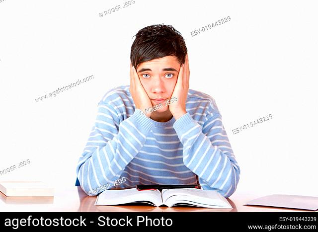 Young handsome sad male student learns with study books