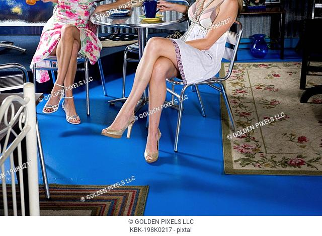 View of sexy legs of two women sitting in a cafi