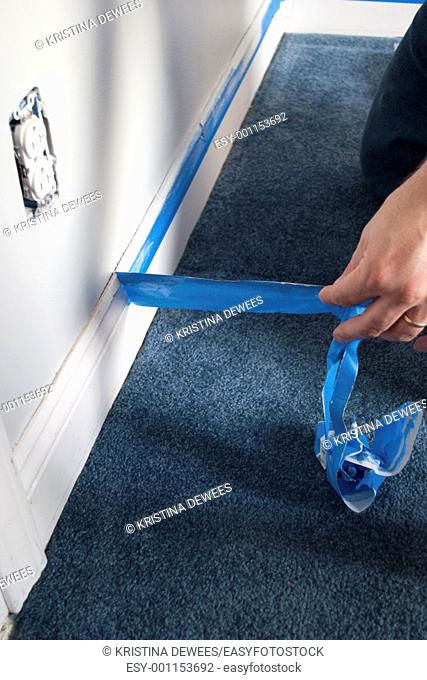 A hand removing blue painters tape after the paint has dried in a room
