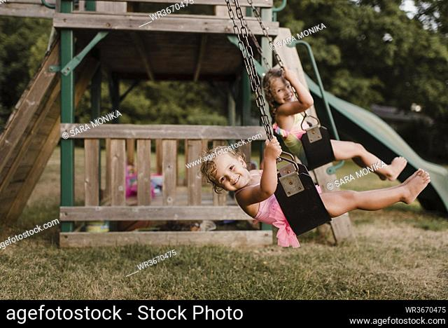 Happy girls with wet hair on a swing