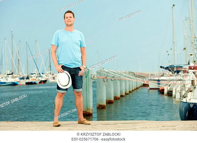 travel tourism vacation and people concept. fashion portrait of handsome man on pier against yachts in port