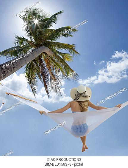 Caucasian woman sitting in hammock under palm tree