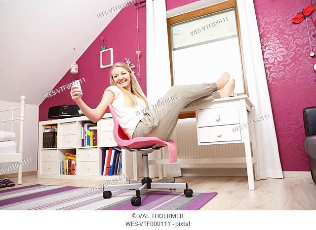 Happy teenage girl at her room using smartphone