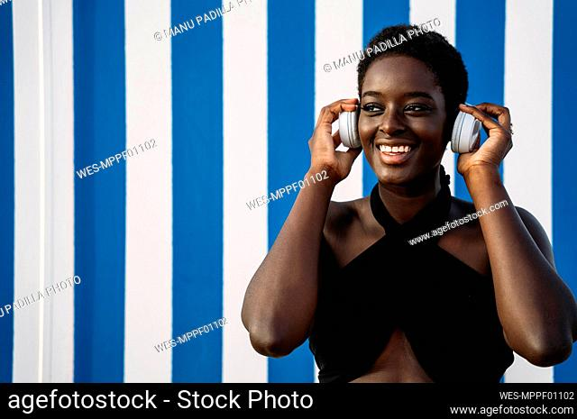Young woman listening music while standing against multi colored wall