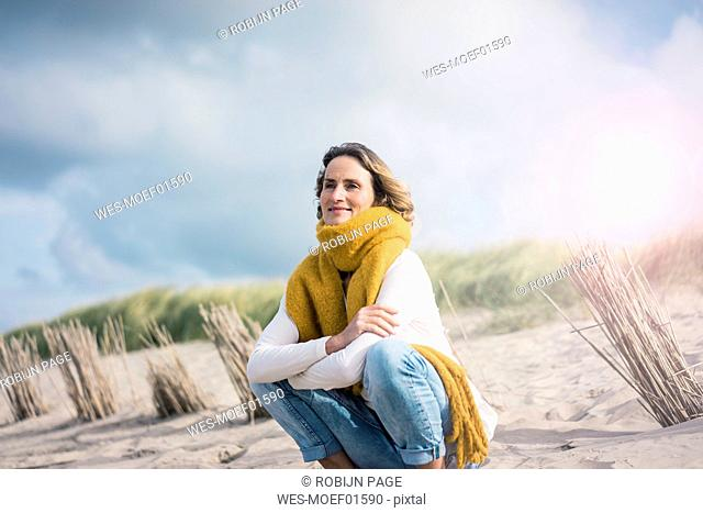 Mature woman crouching in the dunes, enjoying the wind