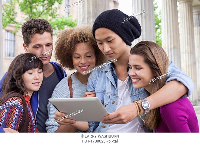 Young man showing digital tablet to multi-ethnic friends