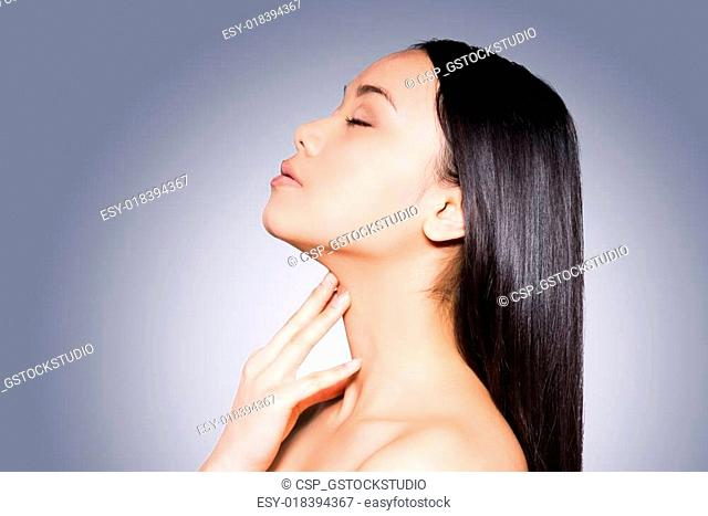 Lustrous hair and perfect skin. Side view of beautiful young and shirtless Asian woman touching her neck and keeping eyes closed while standing against grey...