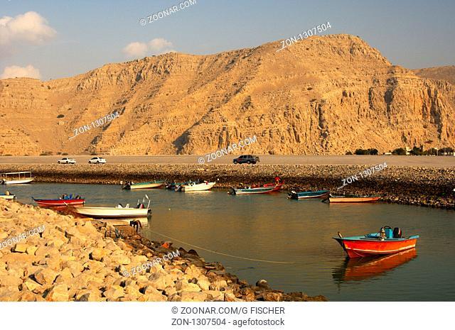 Motoboote ankern in einem geschützten Kanal des Hafens von Khasab inmitten der kahlen Berge der Halbinsel Musandam, Sultanat Oman / Motorboats moored in a...