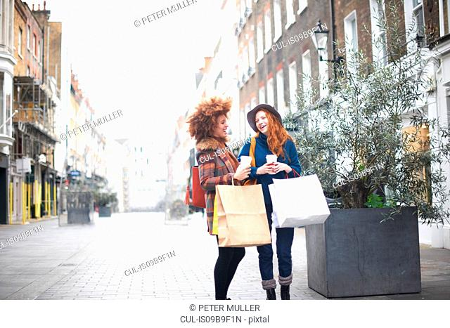 Two young women standing in street, holding shopping bags and coffee cup