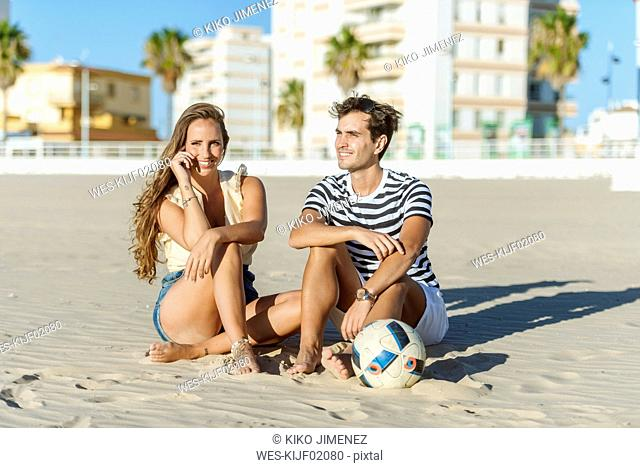 Smiling young couple sitting on the beach with a ball