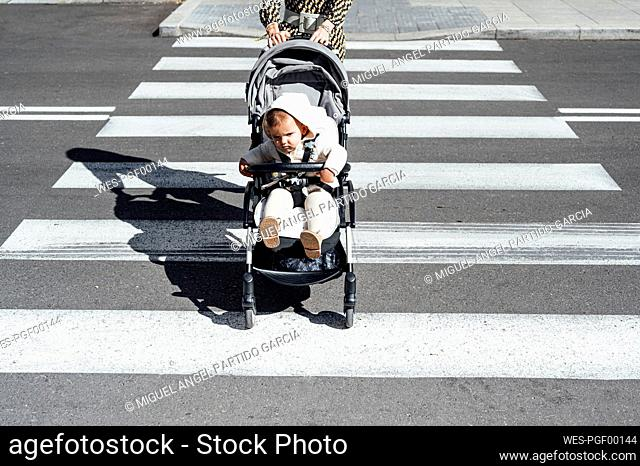 Mother with son in baby carriage crossing street in city on sunny day