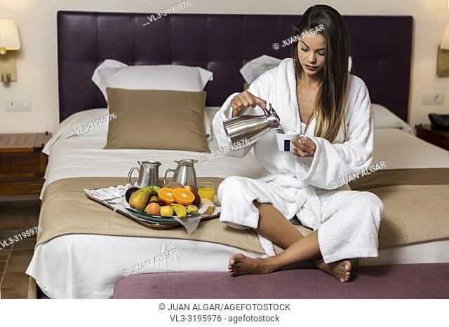 Young woman with dark hair in morning gown sitting on bed of hotel room and pouring coffee in cup with plate of fresh fruits laid near