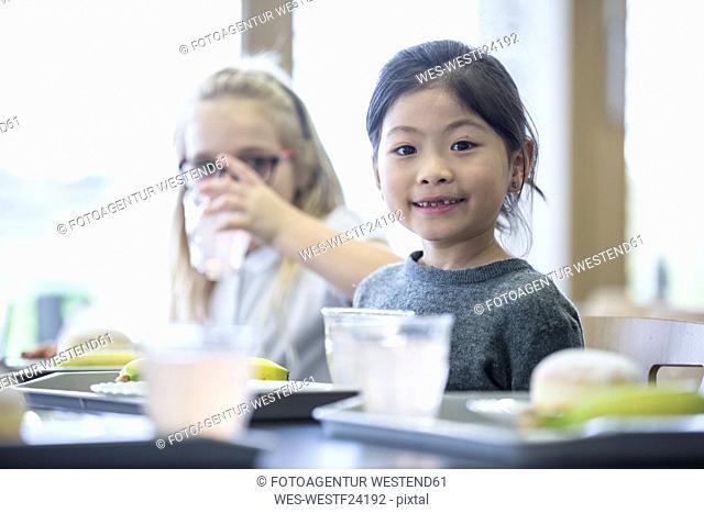 Portrait of smiling schoolgirl with classmate in school canteen