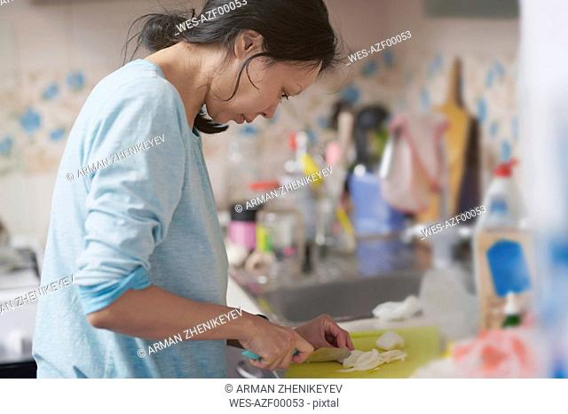 Woman chopping onion in the kitchen
