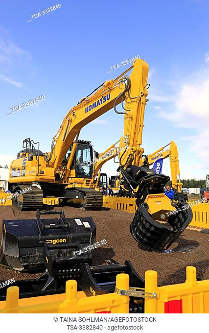 Hyvinkää, Finland. September 6, 2019. Komatsu HB 215 LC Hybrid excavator operator shows great precision by picking pack of cards with the grapple