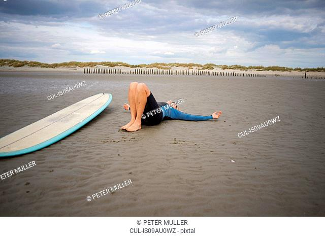 Senior woman relaxing on sand, surfboard beside her