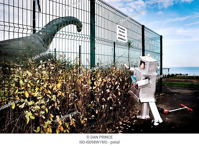 Boy dressed as robot feeding model dinosaur crisps through fence