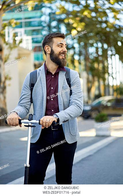 Smiling businessman with scooter on the way