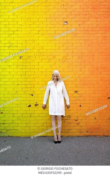 Smiling woman wearing white shirt blouse standing in front of orange wall