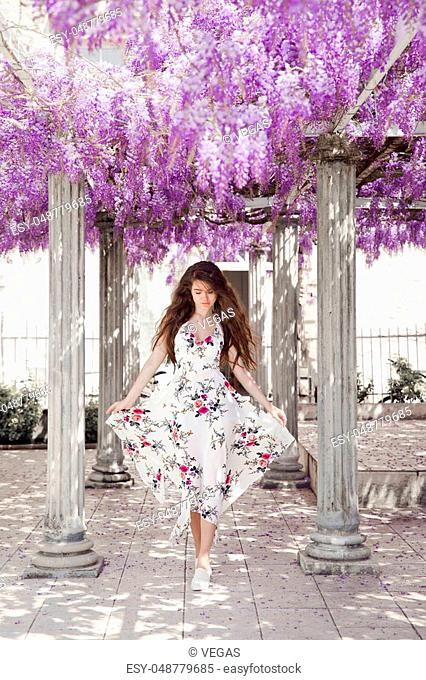 Beautiful young woman in white flying dress over wisteria tunnel arch. Attractive brunette girl with long healthy hair in spring purple park