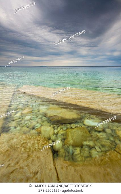 Interesting rock formations beneath crystal clear waters with extreme storm clouds overhead. Bruce Peninsula National Park, Ontario, Canada