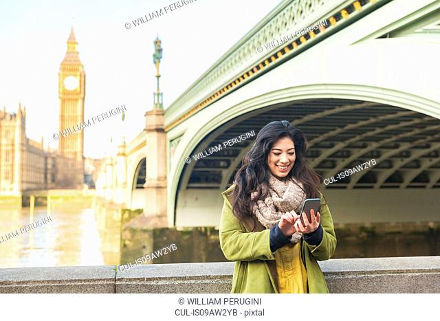 Young woman in front of Westminster bridge and Big Ben looking down using smartphone smiling, Thames river, London, UK