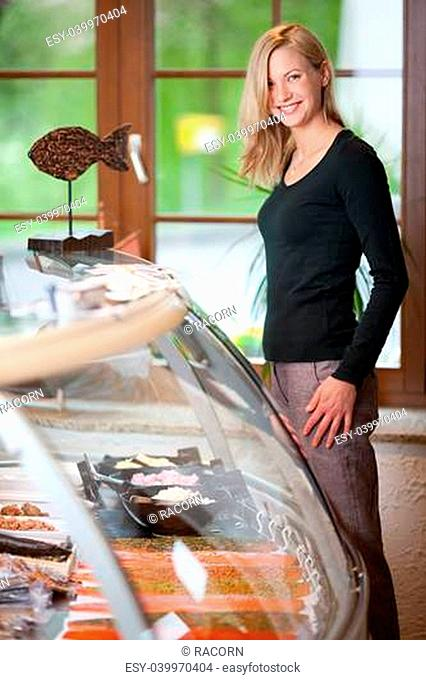 Portrait of happy young woman standing by display cabinet at fish store