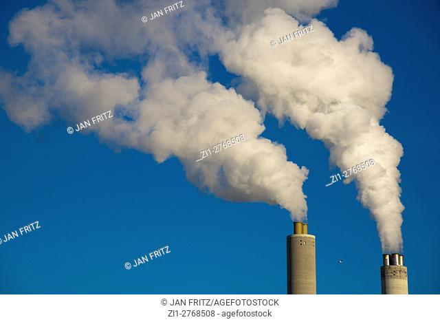 chimneys with white smoke against blue sky at power station in Amsterdam, Holland