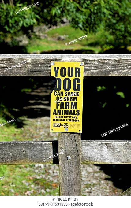 England, Cumbria, Elterwater. Warning sign for dog walkers on a wooden gate