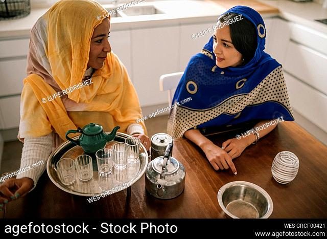 Female friends preparing tea while sitting in kitchen at home