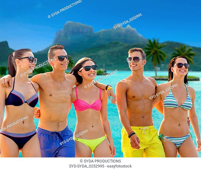 smiling friends in sunglasses on summer beach