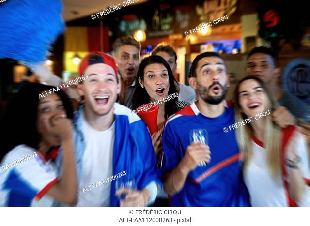 French football fans watching soccer match on television at pub