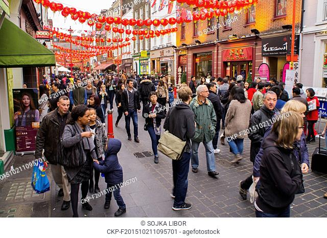 Pedestrians pass under red paper lanterns and red flags of China, Wardour Street in London's Chinatown district, United Kingdom, on Sunday, October 18, 2015