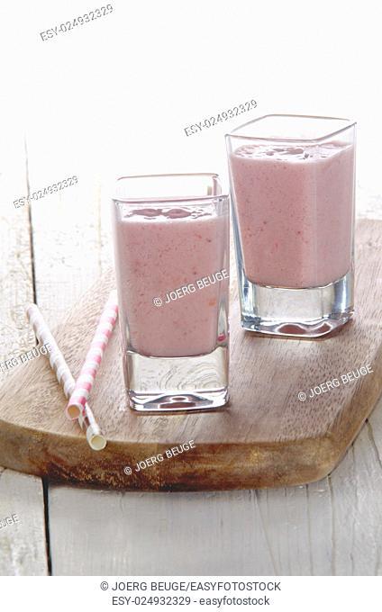 strawberry milk shake in a shot glass with straw