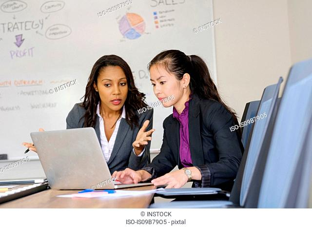 Two businesswomen in office, looking at laptop screen