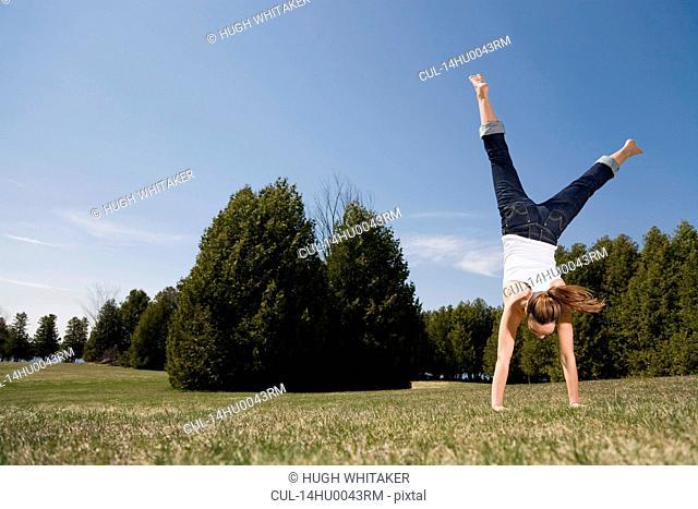 Woman cartwheeling in park